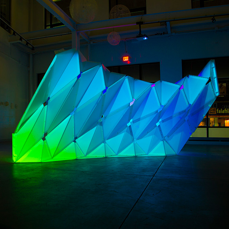 An architectural structure lit with blue and green light.