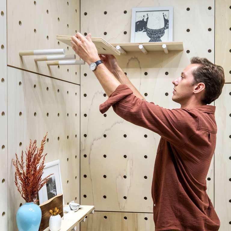 A person installs a shelf.