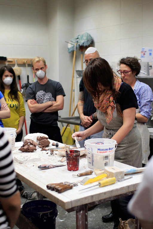 A person leads a ceramics demonstration.