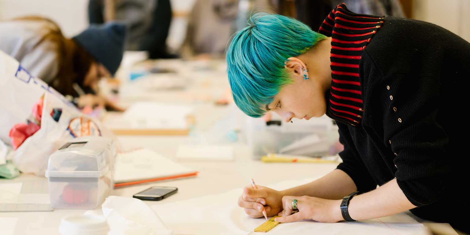 A student with blue hair works on a long table.