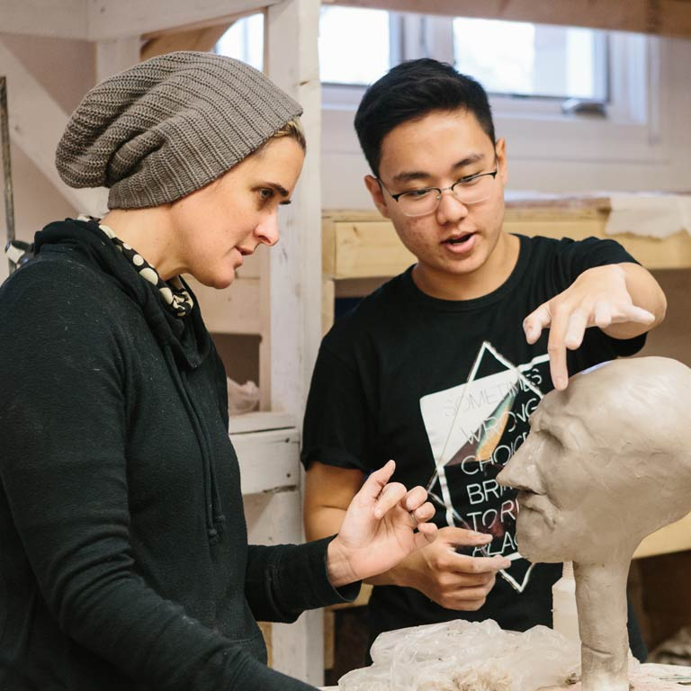 A professor works with a student on a sculpture of a face.