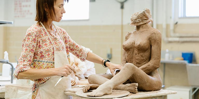 A person works on a sculpture of a woman's body.