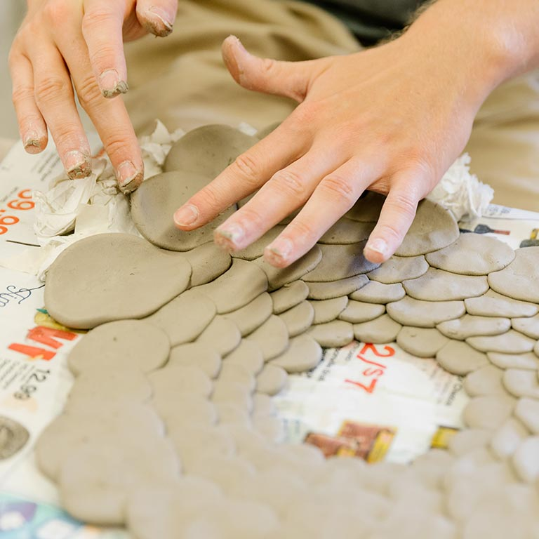 A person works with circles of clay.