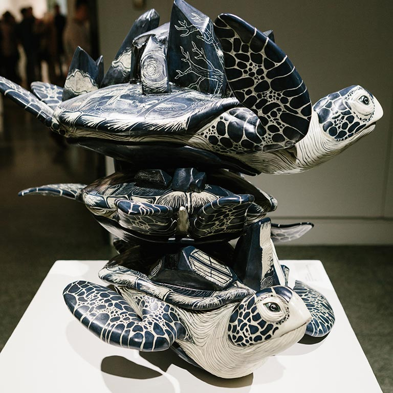A sculpted piece of three turtles on top of each other.