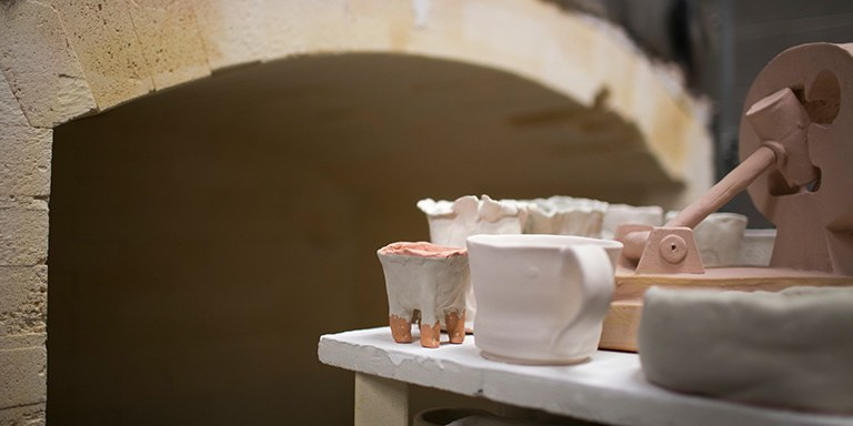 Ceramic pieces in front of a kiln.