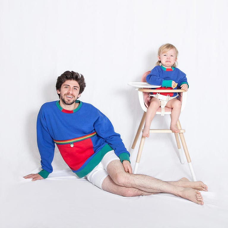 An adult and a child in a high chair look at the camera wearing matching sweaters.