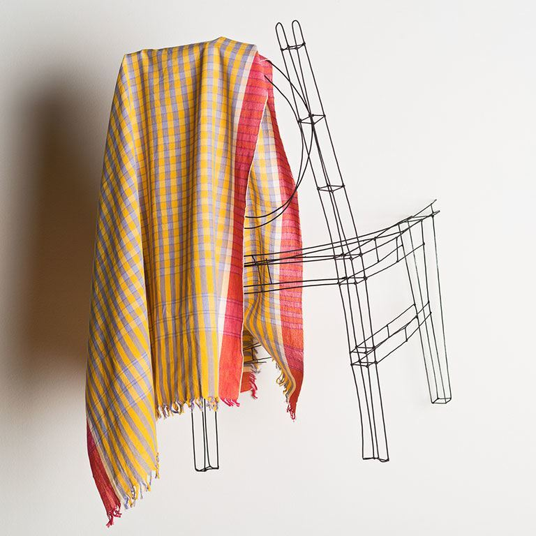 A plaid fabric hangs on a chair.