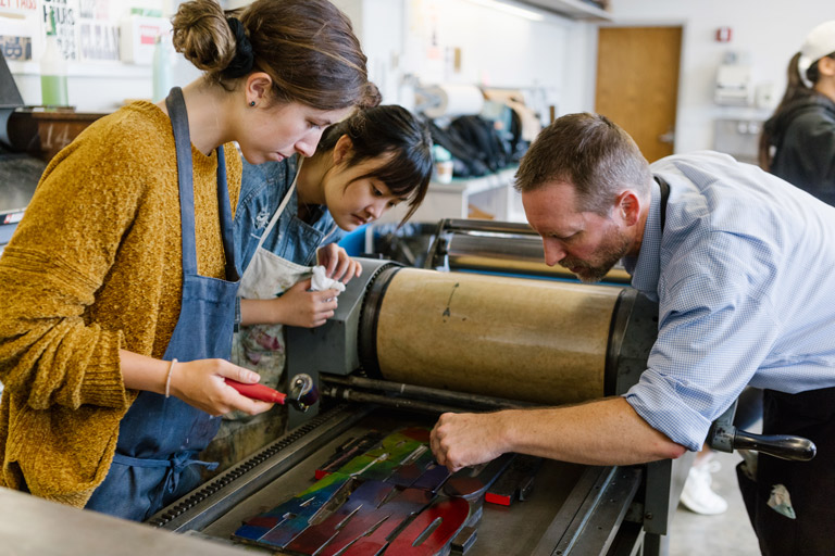 A professor and students work at a letterpress.