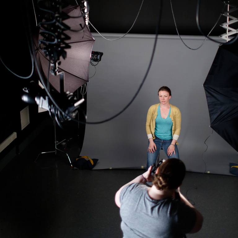 A person poses in a photo studio.