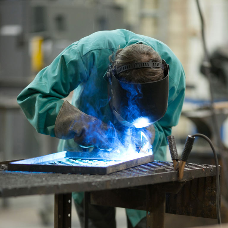 A person using a blowtorch on metal.