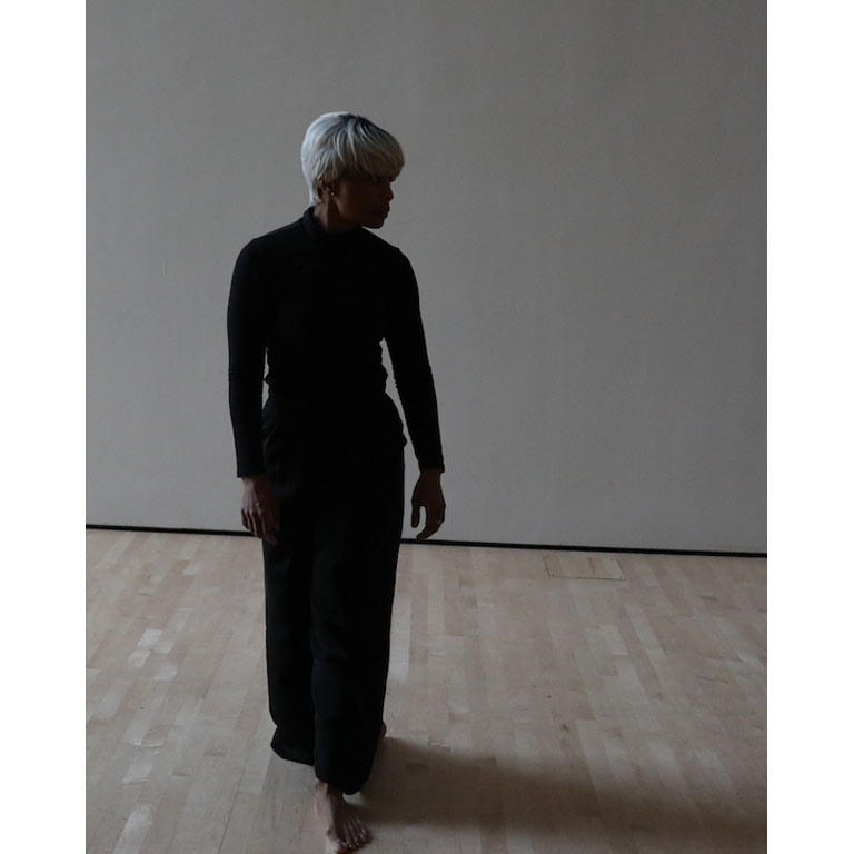A woman in a black dress in an empty room