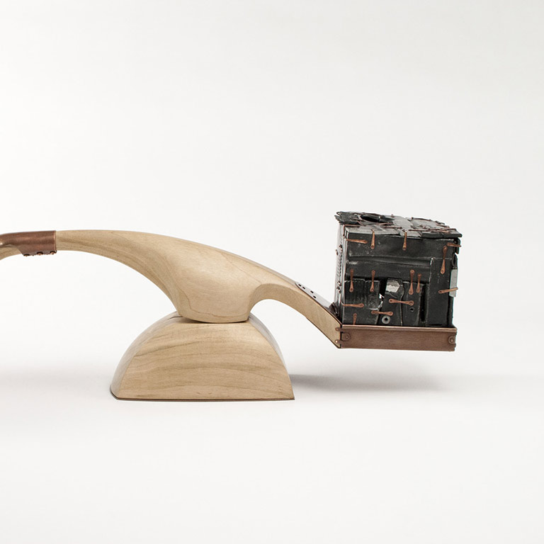 A wooden scale with a metal sculpture on one end.