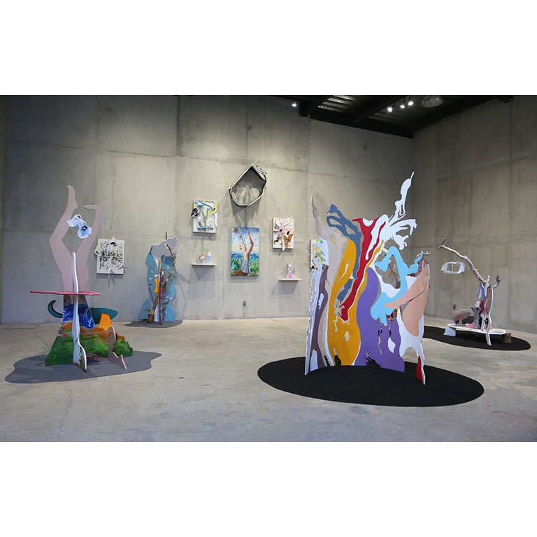 Multiple colorful sculptures in a cement art gallery