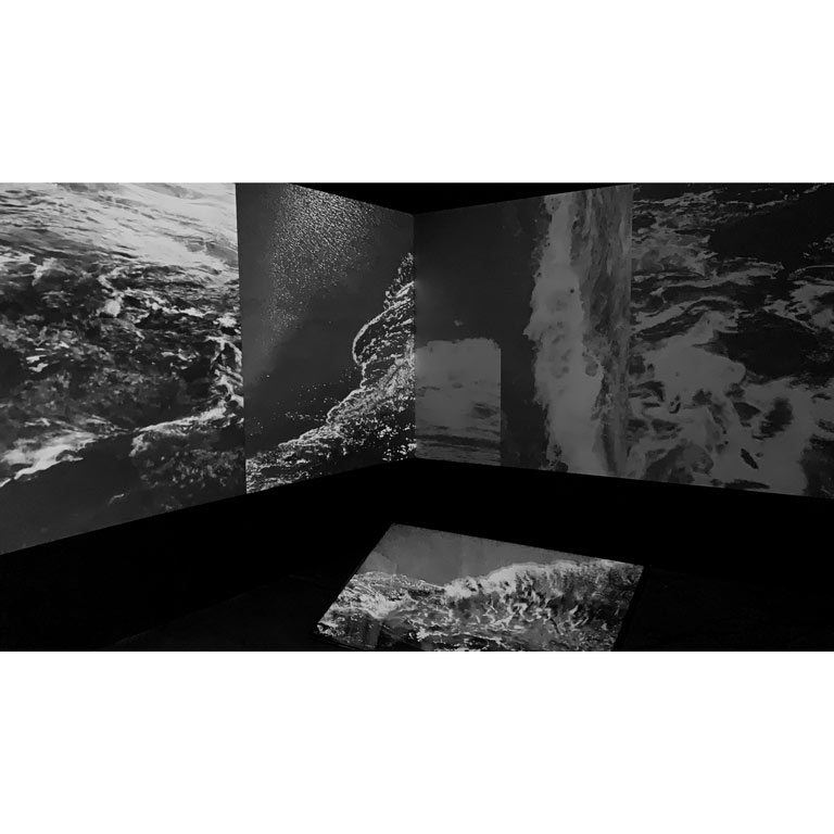 Ocean waves projected on multiple screens in black and white