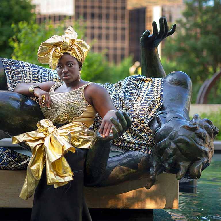 A person dressed in gold sits on a statue of a person laying down.