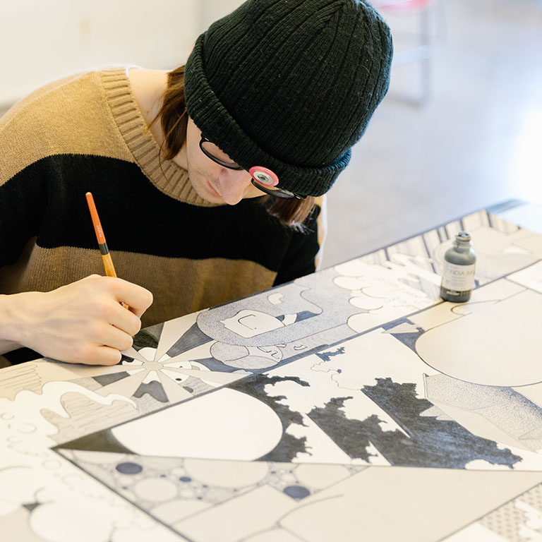 A person draws with a pencil at a table.