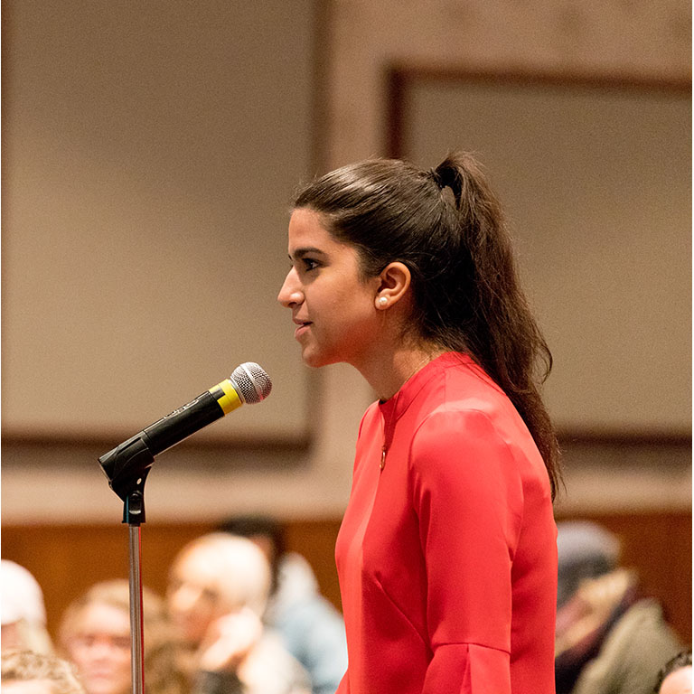 A person speaks into a microphone.