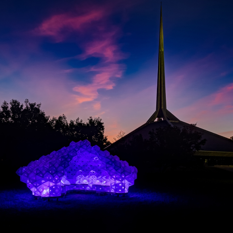 A purple sculpture lit up at dusk.