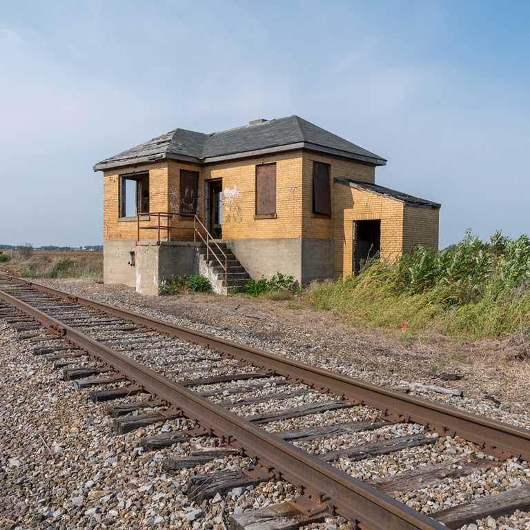 An abandoned brick building alongside a railroad.