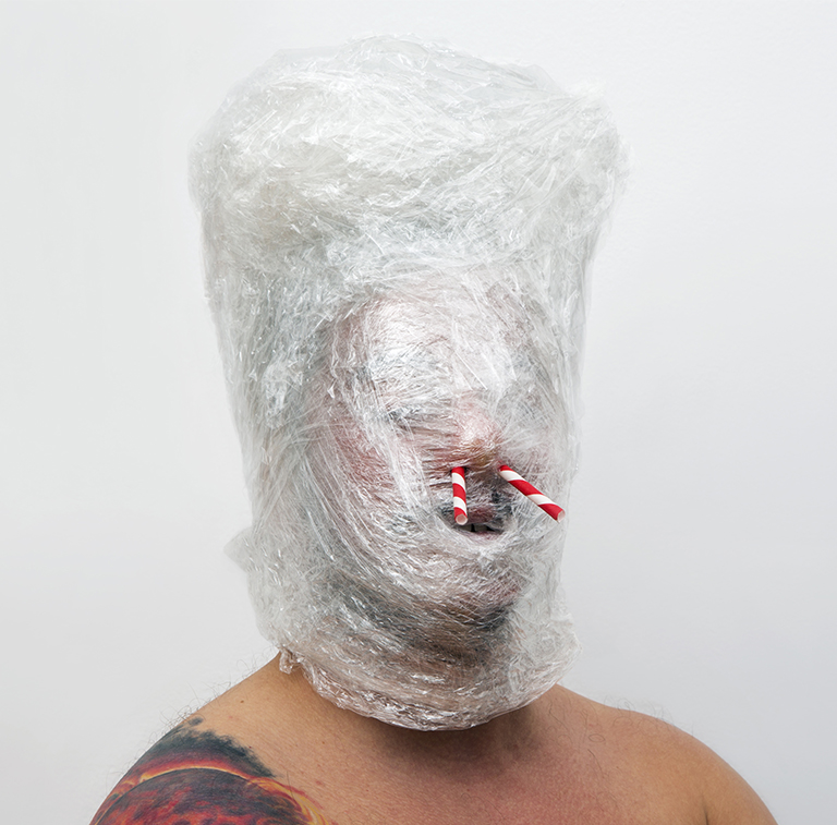 A sculpture of a face wrapped in saran wrap with straws in its nose.