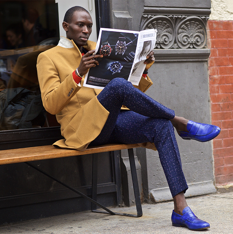 A well-dressed man sits on a bench reading the newspaper.