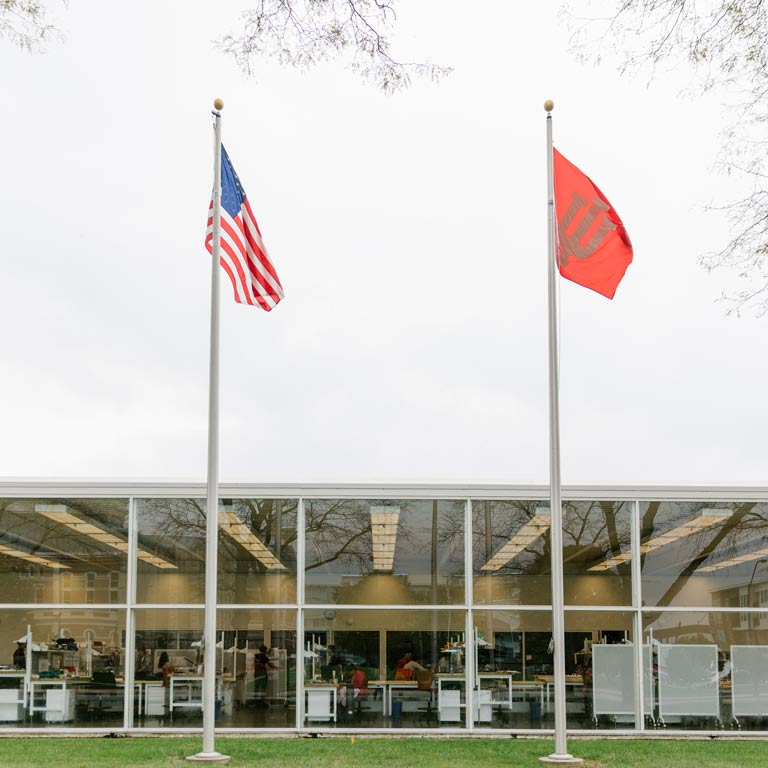 Two flags in front of a glass building