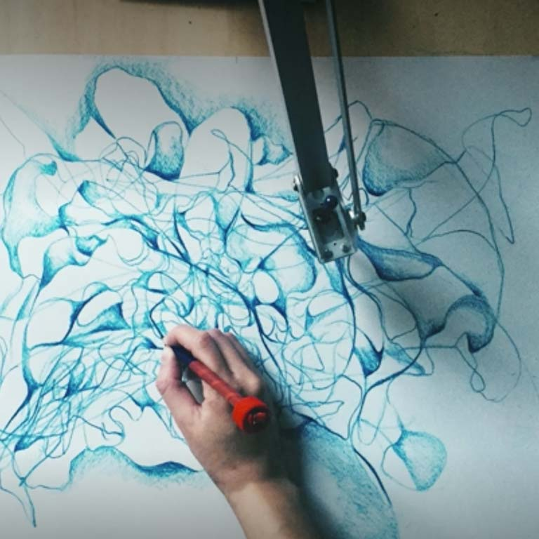 An image of a person drawing with the help of a robotic arm