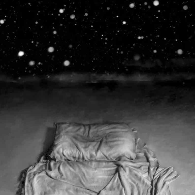 Snowy dark sky above a pillow and blanket.