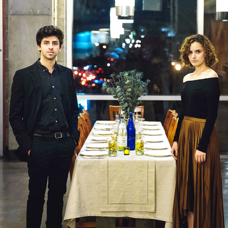 Two people stand next to a dining table set for 10.