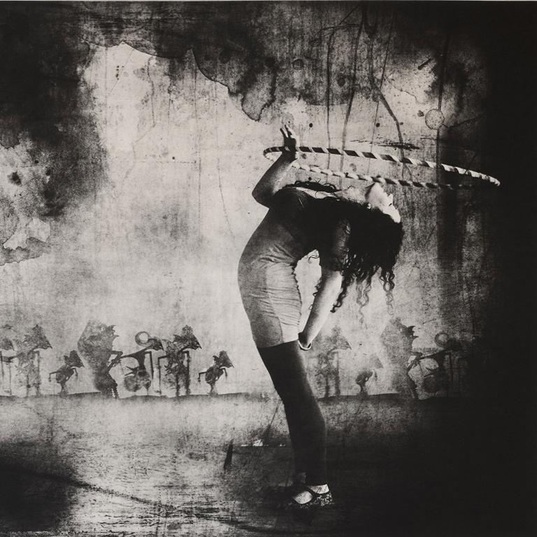A black and white image of a woman with a hula hoop