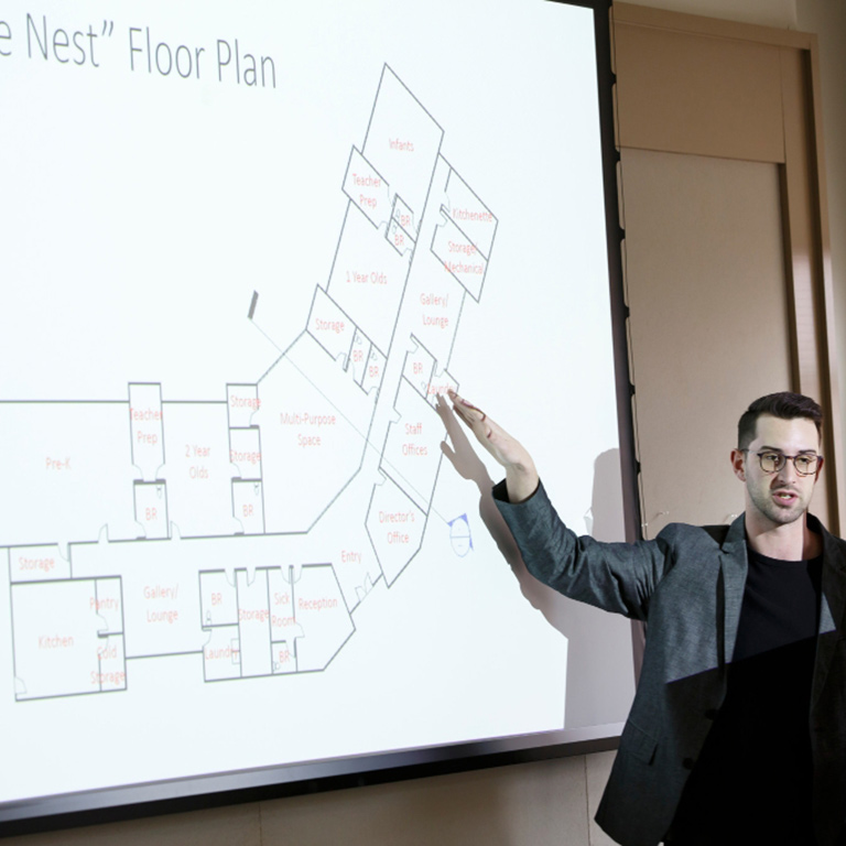 A person points to a floor plan on a wall