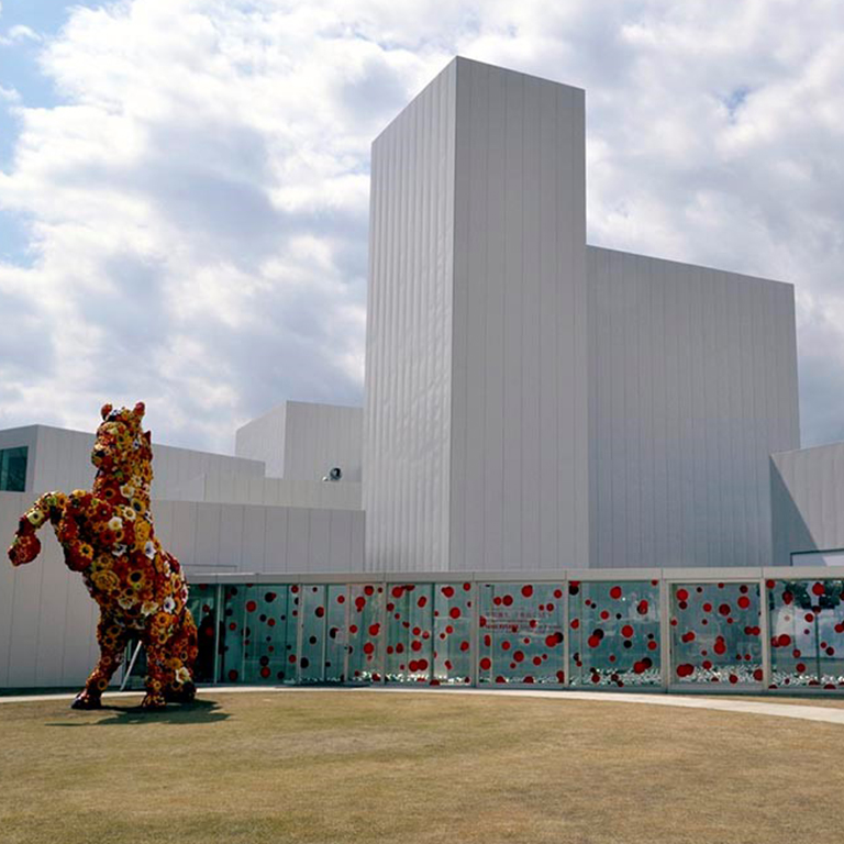 A white building with a sculpture of a horse covered in flowers in front of it.