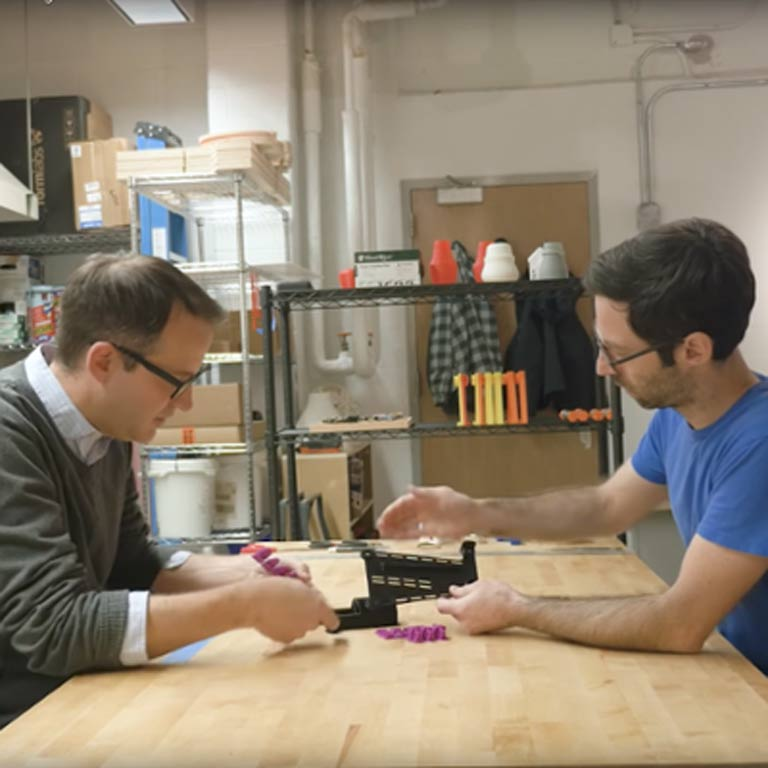 Two people sit at a table working on a prosthetic arm.