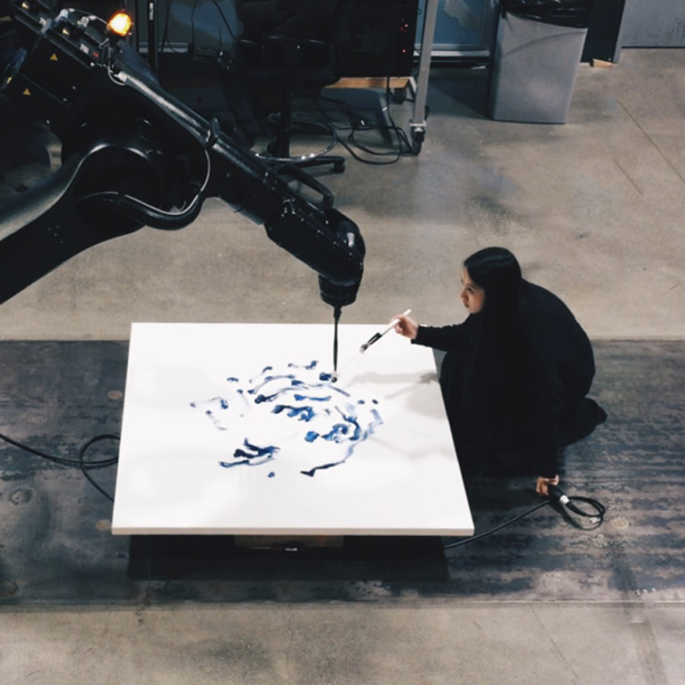 A person paints a canvas which is also being painted by a robot holding a paint brush