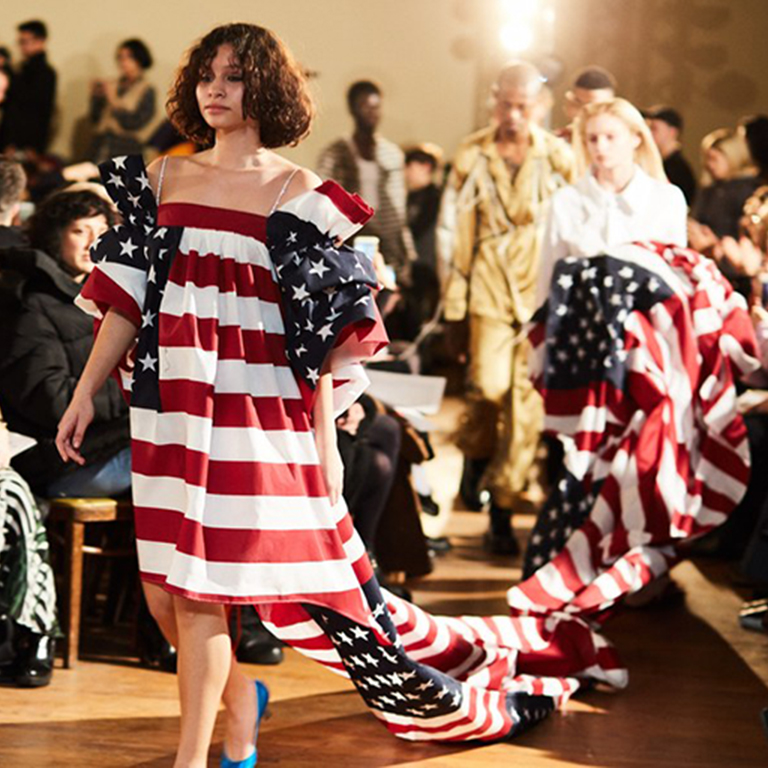 A person walks in a dress that looks like the American flag