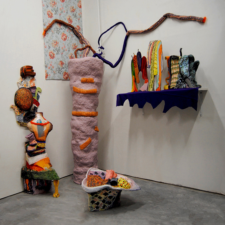 Colorful sculptures in the corner of a gallery.