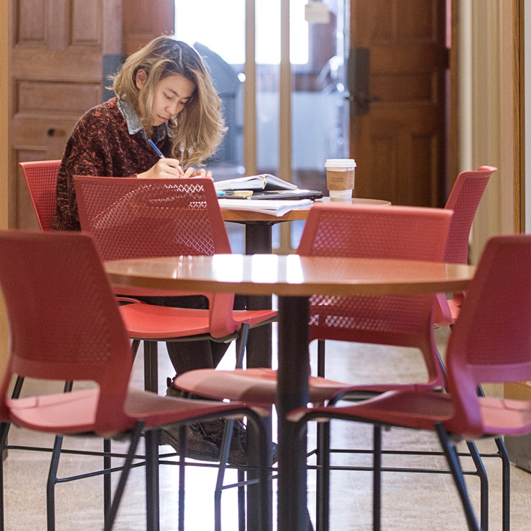 A person studies at a table with red chairs.