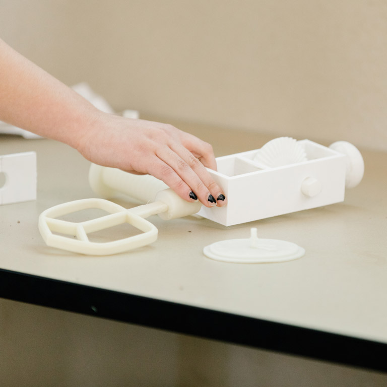 A person reaches for a white 3D printed object.